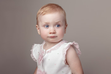 Closeup portrait of cute adorable white blonde Caucasian baby with blue eyes girl looking in camera. Charming child girl posing in studio on plain light background.