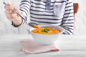 Young woman eating delicious carrot soup from bowl