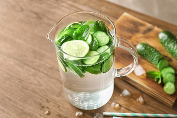 Delicious refreshing water with mint and cucumber in jar on wooden table
