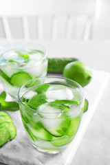 Delicious refreshing water with mint and cucumber in glass on marble board