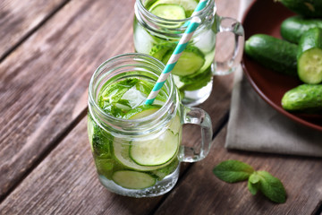 Delicious refreshing water with mint and cucumber in mason jars on wooden table