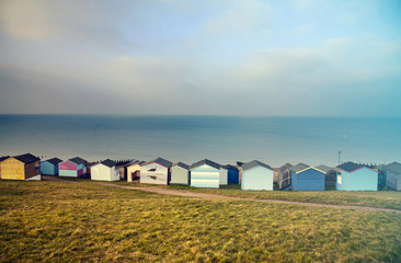 Blue sky and colorful beach huts along the coastline of Whitstable - retro styled photo