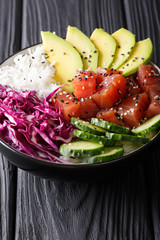 Tuna poke bowl with rice, cucumber, red cabbage and avocado close-up. vertical