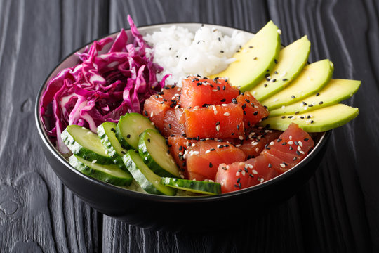Organic food: tuna poke bowl with rice, fresh cucumbers, red cabbage and avocado close-up. horizontal