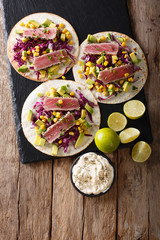 Tacos with tuna steak and fresh vegetables close-up. Vertical top view