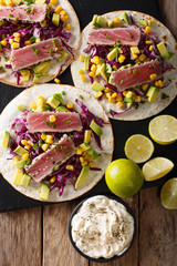 Mexican tacos with tuna, red cabbage, corn, avocado and onions close-up. Vertical top view