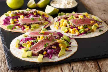 Tacos with tuna steak and fresh vegetables close-up on the table. horizontal