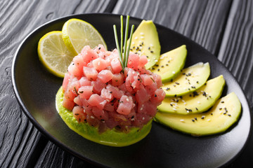 tartar of fresh tuna with spices, lime and sesame close-up on a plate. horizontal