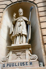 Statue of St Publius in an alcove on the front of the Parish church of our lady of sorrows, Bugibba, Malta.