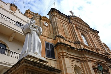 Front view of the Parish church of our lady of sorrows with a statue in the foreground, Bugibba, Malta.