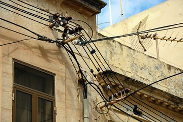 Electricity cables and a TV aerial on the front of a building, Bugibba, Malta.