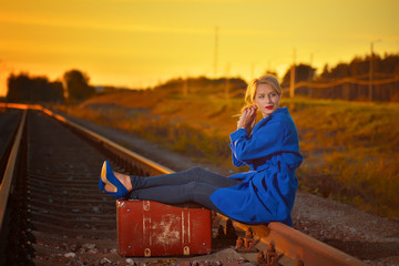 blond woman in blue coat posing on railraod