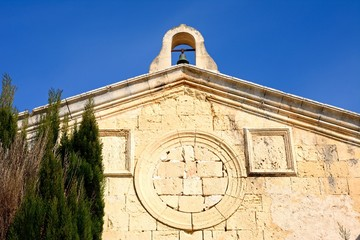 Small bell tower on top of an old church with a bricked in round window in the city centre, Mdina, Malta.