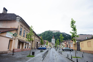 Rasnov, Romania.  View of the Rasnov city mainstreet (Brasov county (Romania), with the hill of the medieval Rasnov fortress and the city name in the Hollywood style