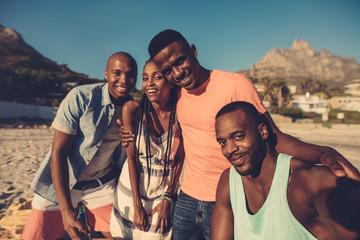 Group of friends taking selfie on the seashore.