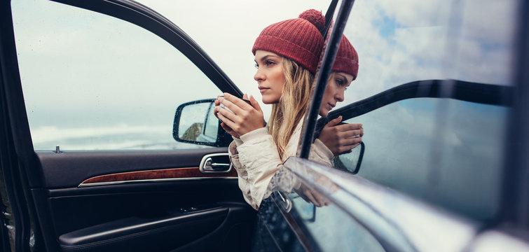 Female on road trip drinking coffee inside car