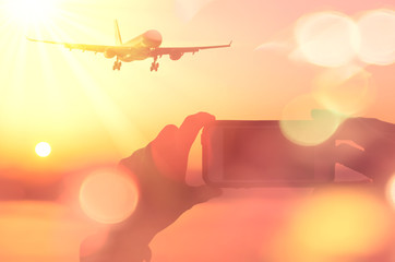 Woman hand take photo airplane flying over sunset beach double exposure colorful bokeh light abstract background.