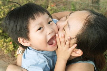Happy mother embracing and kissing her son : Close up