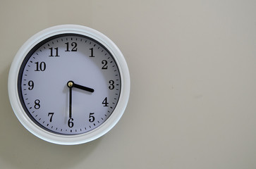 Time of the wall clock hung on a wall is 3:30.
