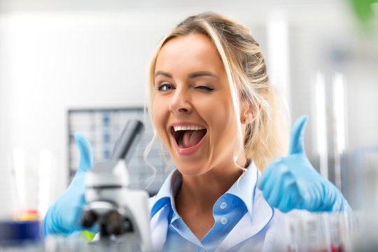 Young attractive smiling woman scientist is happy with her work