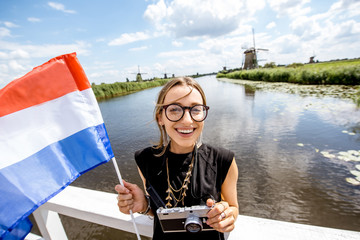 Young woman tourist standing with dutch flag on the beautiful landscape backgorund with old windmills in Netherlands
