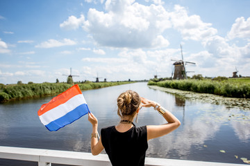 Young woman tourist standing back with dutch flag enjoying great view on the beautiful landscape with old windmills in Netherlands