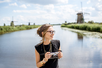 Portrait of a young woman tourist standing with photo camera on the beautiful landscape background with old windmills in Netherlands