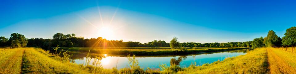 Fototapete - Sommerliche Landschaft mit Fluss bei Sonnenuntergang