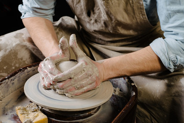 pottery, workshop, ceramics art concept - closeup on male hands sculpt new utensil with a tools and water, man's fingers work with potter wheel and raw fireclay, front close view
