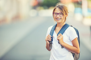 Schoolgirl with bag, backpack. Portrait of modern happy teen school girl with bag backpack. Girl...