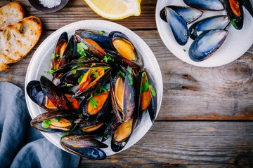 Acrylic Prints Seafoods Delicious seafood mussels with with sauce and parsley. Lemon and baguette . Clams in the shells.