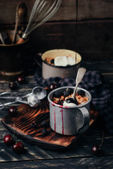 Crumbles of oatmeal, cherries, blackberries and black currants with vanilas ice cream and chocolate topping in vintage metal mugs on a black wooden background. Close up. Toned picture
