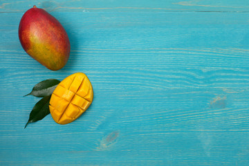 Whole mango and cut into pieces on a blue wooden background