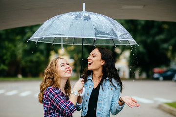 Two joyful hipster girl sheltering from rain beneath umbrella - they loves a rain and rejoices. Large rain drops fall on an umbrella dome.