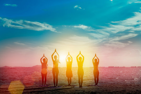 Young group man and woman yoga practice on mat relaxation in class exercise with pose fitness sport for healthy on the beach and seaside  modern city at sunrise relax holiday vacation time in summer.