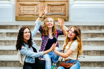 Three female laughing students makes Hi by hands while sitting outdoor on university steps - education, school, teamwork and people concept