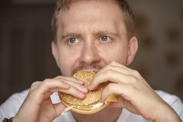 Man eating hamburger with vegetables at a fast food restaurant, fast food knowns like unhealthy food in the world