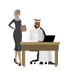 Arabic businessman working at a laptop and business woman standing