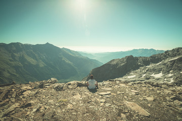 One person sitting on rocky terrain and watching a colorful sunrise high up in the Alps. Wide angle view from above with glowing mountain peaks in the background. Toned image.