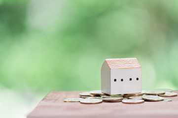 Saving money for house,golden coins and house model on wood table with green blurred background