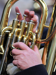hand of man plays the trombone in the brass band