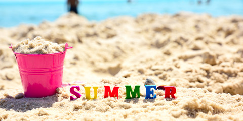 multicolored wooden letters in the word summer on sand