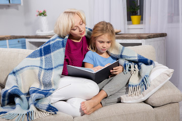 Mother and daughter sitting on couch under blanket. Caring mom reading to her sick daughter.