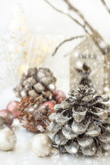 White Christmas decoration composition, big pine cones, scattered baubles, shiny star, wooden candle holder, dry tree branches in background, minimalist style