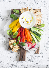 Raw vegetables and yogurt sauce on a wooden cutting board, on a light background, top view. Vegetarian healthy food concept