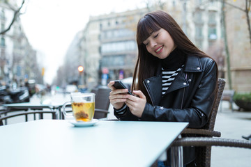 Pretty Long Hair women smiling and browsing her smartphone