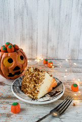 cute pumpkin with candy and slice of pumpkin spice cake