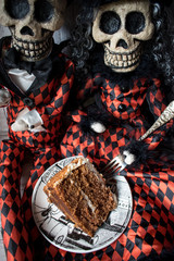 Halloween skeletons with a slice of spice cake