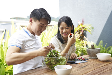 Couple tossing their salad in the outdoor balcony