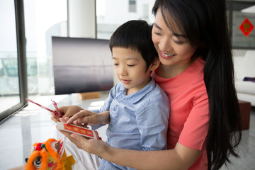 Mother and son holding traditional Chinese New Year decoration